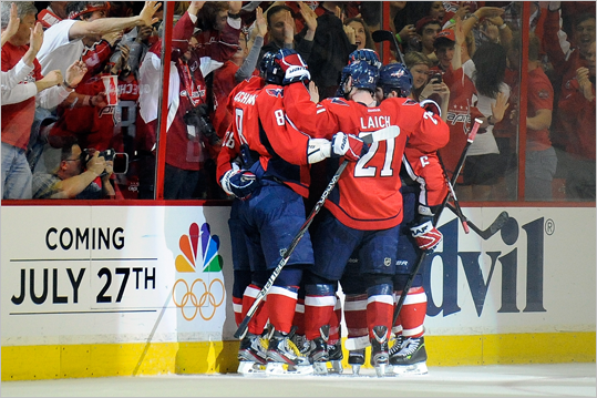 Alexander Semin celebrated with Alex Ovechkin, Dennis Wideman, and Brooks Laich of the Capitals after scoring a goal