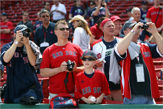 Fans shoot photos of Red Sox players taking batting practice before the 100th anniversary.