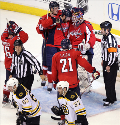 Capitals goalie Braden Holtby and the Capitals celebrated after evening the series at 2 with their 2-1 win over the Bruins as Brad Marchand and Boston's Patrice Bergeron skated off the ice.