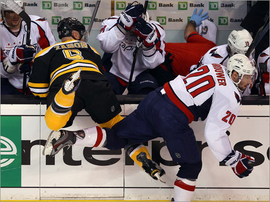 The Bruins' Greg Zanon got checked into the Capitals bench Troy Brouwer.