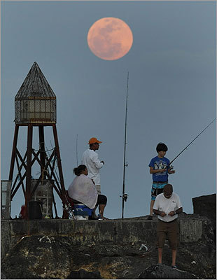 People fished from a jetty as the moon rose in Bal Harbour, Fla.