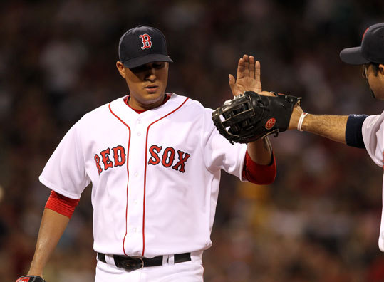 Red Sox starting pitcher Felix Doubront (61) was congratulated by first baseman Adrian Gonzalez (28) at the end of the sixth inning.