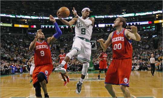 Rondo dumped off the ball as he was pressured by Andre Iguodala (left) and Spencer Hawes during the first quarter.
