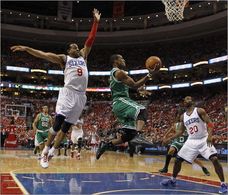 Rajon Rondo shot between the defense of Andre Iguodala (left) and Jodie Meeks. Rondo scored 23 points and had 14 assists as the Celtics crushed the 76ers.