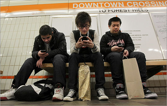 MBTA riders used their cellphones at the Downtown Crossing Orange line platform. Officials predict complete cellular service for all underground portions of the subway will be fully wired by the end of the year.