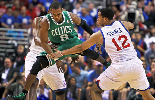 Celtics guard Rajon Rondo was able to control the ball after he had just started to dribble off of a first quarter loose ball, sailing between the 76ers Elton Brand (left) and Evan Turner (right) and he continued to bring the ball up court for Boston.
