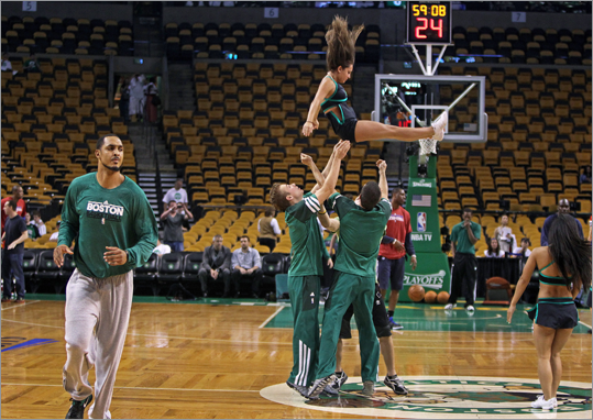 The Celtics Ryan Hollins (left) got loose before the game, as did members of the 'Green Team', (right) the Celtics gymnastics troupe.