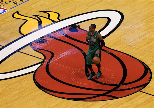 Rajon Rondo (9) called a play as he dribbled past the Heat logo during the second quarter.