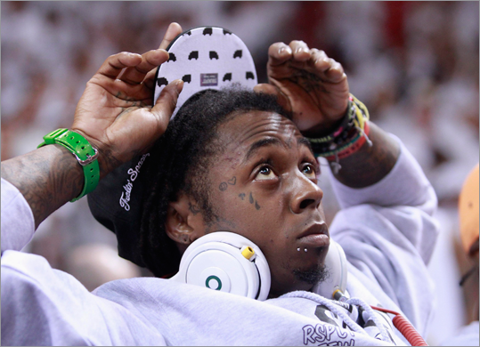 rapper Lil Wayne watched a replay while sitting on the sideline.