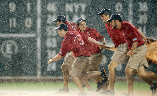 Tuesday, May 29 The Fenway Park grounds crew rolled out the tarp during a rain delay in the eighth inning.