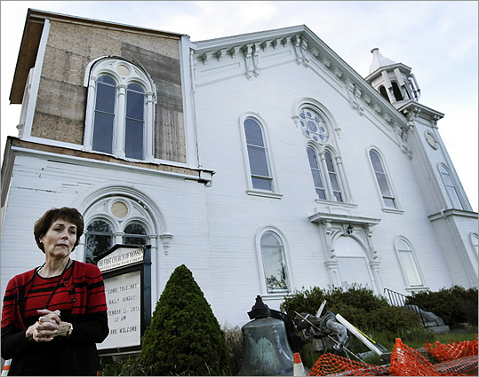 Suzanne Kelley, church board of trustees chair, stood below the damaged clock tower of the First Church of Monson Congregational, a year after a tornado ravaged the town.