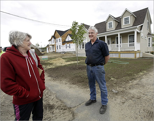 Debbie and Dwight Meacham spoke as they stood in front of their newly built home in Monson, a year after a tornado destroyed homes in their neighborhood.