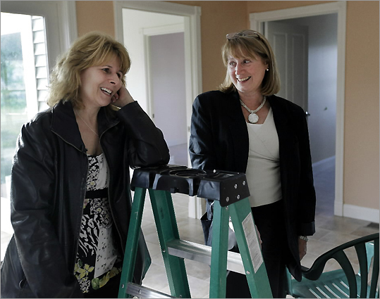 Kim Slozak (left) talked with her neighbor Diana Robbins in Slozak's nearly rebuilt home in Monson. They recalled surviving the tornado that ravaged their homes a year earlier.