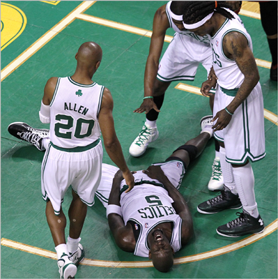 Celtics power forward Kevin Garnett writhed in agony on the parquet after being thrown to the ground battling for a loose ball during the second quarter.