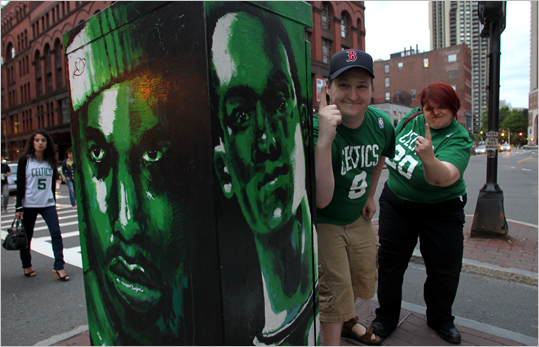 Fans pose next to a pillar with the likeness of Paul Pierce and Rajon Rondo painted on it.