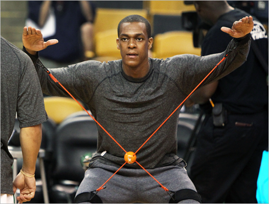 Celtics guard Rajon Rondo used an elastic device to get loose before the game.