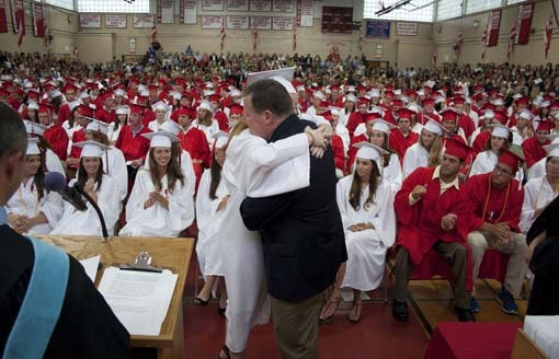 School Committee member Andy Shafter hugs his daughter, Erin, after handing her the diploma.