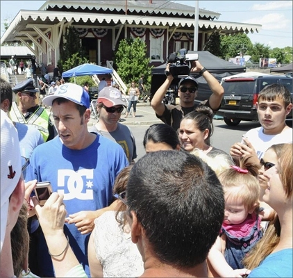 About 100 people stood silently for several hours, staring at the commuter rail platform in Swampscott. Adam Sandler huddled with a group of Hollywood producers and camera operators as a train rolled into a scene that included actors David Spade and Alexander Ludwig. After the final take, Sandler left a gaggle of technicians, crossed the street, and waded into the cheering crowd. He wore a blue T-shirt, baggy silver gym shorts, red sneakers, and a Swampscott Big Blue baseball cap, the same hat he would sport three nights later at the MTV Movie Awards in Los Angeles. Sandler, left, greets his fans between takes.