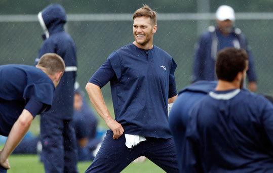 Patriots quarterback Tom Brady smiles while stretching during minicamp.