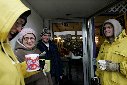 Maria Andersen, Colby Cedar Smith, Blair Schoene, and Eric Saline chuckle as raindrop falls in Maria's coffee cup, as they stand outside at SoundBites in Somerville's Ball Square.