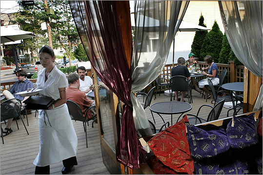 Waitress Lejla Arapcic waits on patrons siting at the porch area of Sabur restaurant located on Holland Street