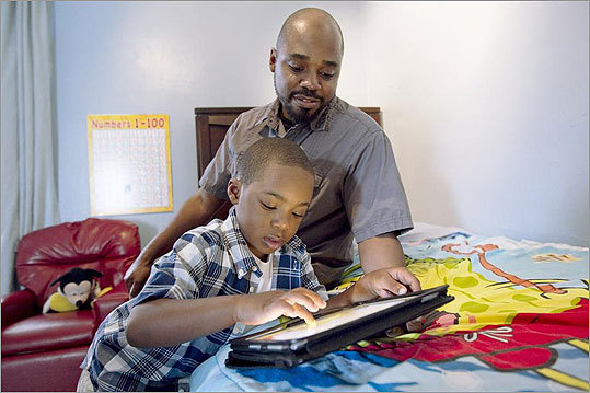 Victor Watch observes his son using an iPad. A phone may come soon.