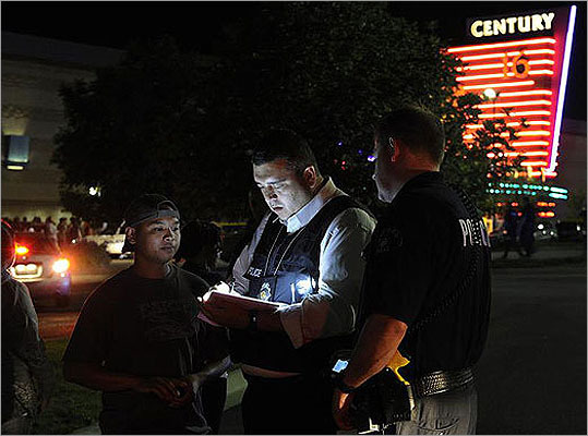 Aurora, Colo. -- July 20, 2012: Twelve people were killed and 58 others were injured when police say James Holmes entered a movie theater, released a canister of gas, and then opened fire during opening night of the Batman movie 'The Dark Knight Rises.' View scenes of the aftermath . Colorado prosecutors charged James Holmes July 30 with 24 counts of murder and 116 counts of attempted murder in the shooting rampage. Holmes's defense attorney said he's mentally ill. Holmes remains held without bail. Pictured: An Aurora Police Department detective took a witness statement following the shooting.