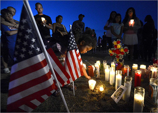 Myia Young, 4, placed a candle by an American flag during a vigil for the shooting victims.