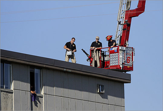 A law enforcement officer placed a silver remote device on a roof top across from the apartment complex where suspect James Eagan Holmes lived in Aurora, Colo. Police sent in a robot to detonate what they called a sophisticated booby-trap in the apartment of Holmes, 24, accused of the shootings.
