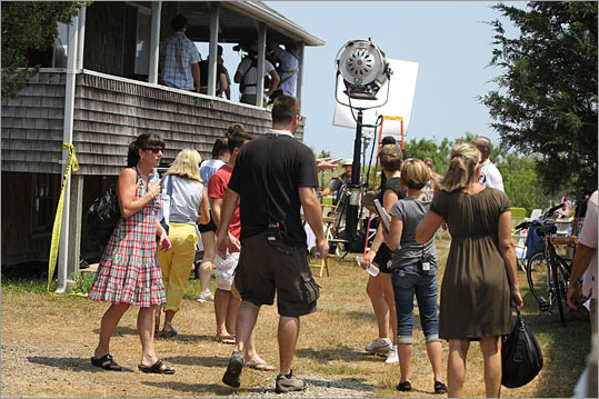 "Dozens of local actors — or ""extras"" — wearing summer beach wear, approved by the wardrobe department, milled around one front yard waiting to be called to appear in the background of a Fourth of July party scene. Meanwhile, two golf carts zipped back and forth, shuttling down Bay Avenue between the set and the trailers stocked with wardrobe and makeup supplies. About 125 people —which includes including cast, crew, and extras — have been working on the movie. Extras and crew at a movie production being filimed in Marshfield's Green Harbor neighborhood ."