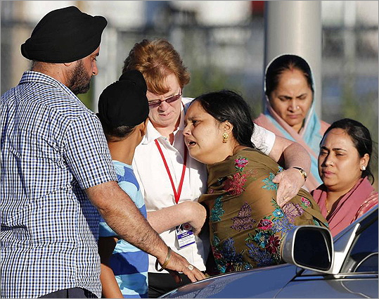 A distraught women was helped to a car outside of the Sikh temple in Oak Creek, Wis., on Aug. 5.
