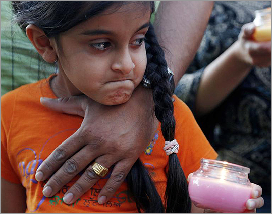 Bani Kaur held a candle as she stood with her father, Manjeet Kaur, during a candlelight vigil for victims of a shooting at a Sikh temple, at Cathedral Square in downtown Milwaukee on Aug. 5.