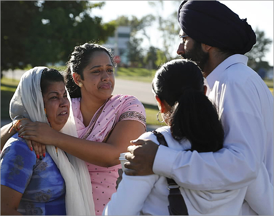 People consoled each other at the command center near the Sikh Temple of Wisconsin on Aug. 6.