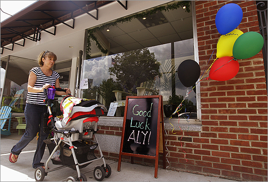 A woman pushing a baby carriage walks past a shop with a sign recognizing U.S. gymnast Aly Raisman in her hometown of Needham, Mass., Wednesday, Aug. 1, 2012. It seems as if everyone in this Boston suburb is rooting for Raisman, the captain of the U.S. women's gymnastics team that captured Olympic gold Tuesday in London. Her friends, acquaintances and even those who don't know her say they are riveted to their TVs.