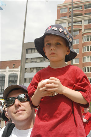 Duff White of Attleboro holds his four year old son Eryk on his shoulder as the crowd begins to build. Eryk brought a baseball that Damon later signed.