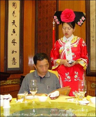 A waitress dressed in beautiful Qing dynasty (1644-1911) fashion with a modern wireless PDA takes an order.