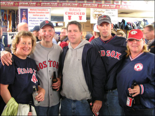 "Nothing like invading an enemy bar to bring Sox fans together. From left to right, Laurie Krusas and Bill Peterson of Sturbridge and Mark Gorman of New City, NY, pose with Bobby and Kelly Butts of Dorchester, who they didn't know until 10 seconds before the photo was taken. They're in Ball Park Lanes, a bar/bowling lane across the street from Yankee Stadium. ""There's people here from Boston that we thought,"" Kelly said. About a third of the people in the bar were in Sox gear."