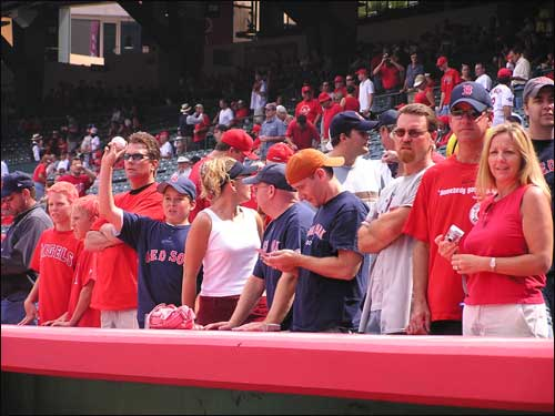 Red Sox fans seek a pregame autograph from players atop the Boston dugout.