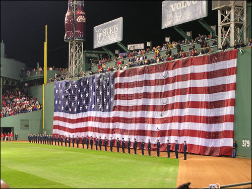 In what has become a Fenway Park tradition for big games, the Stars and Stripes was draped over the Green Monster for the National Anthem.