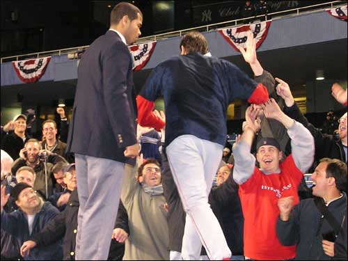 Lefty specialist Mike Myers uses both hands to high-five Red Sox fans behind the visiting dugout at Yankee Stadium.