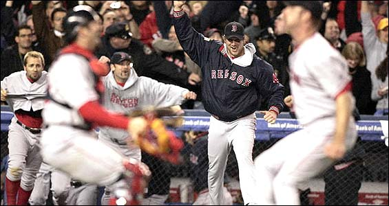Alan Embree and Jason Varitek prepare to embrace, while the rest of the Red Sox -- including winning pitcher Derek Lowe -- pour onto the field.