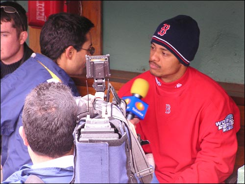 Orlando Cabrera sits in the dugout for a Spanish-speaking radio interview.