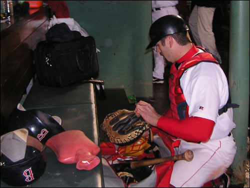 Jason Varitek packs up his gear for St. Louis as Curt Schilling's hot water bottle remains on the bench. Varitek's smash two-RBI triple in the first inning with two out got the Sox off on the right foot in Game 2.