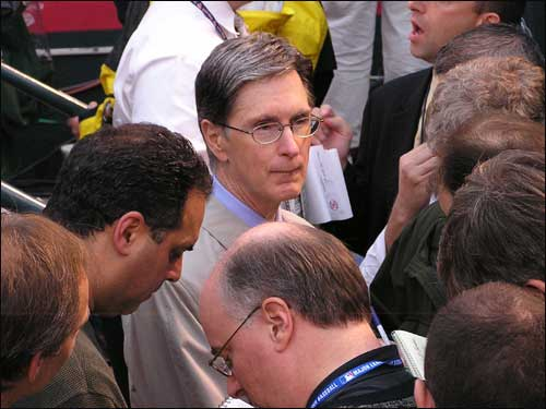 Red Sox owner John Henry meets with a throng of reporters in the Red Sox dugout.