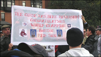 """Saul Farber of Boston and Paul Nutting of Dorchester unfurled this banner on the State House steps. It reads, """"The curse has been reversed! Congratulations World Champion Boston Red Sox."""""""