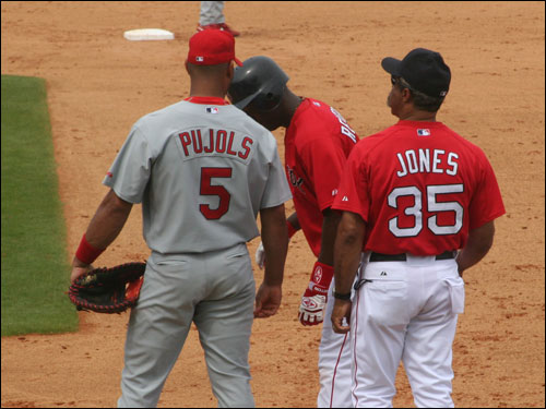 Albert Pujols has a word with old friend Edgar Renteria at first base. Edgar's new team picked up where they left off in the World Series, hammering St. Louis 9-3.