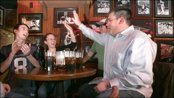 Jay Ceresia high-fived Heather Desimone as they and teammates Richie Conlon (left) and Matt Calvey celebrated a right answer at Pizzeria Uno's trivia night in Cambridge.