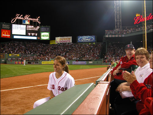 Serving as ball attendant, Kelly Barons laughs with patrons along the right field line. It's easy for her to laugh. She gets paid to sit there. Their seats cost $250 a piece.