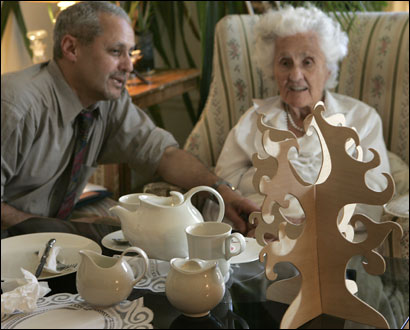 Eva Zeisel, 98, sits with her son Jon Zeisel at a table displaying some of her creations.