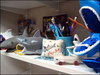 The sharks shown here, on display in Arthur 'Shark' Johnson's office in the Back Bay, are just a small portion of his vast collection of sharks, which he has amassed over the last 15 years. The little embroidered pillow in the middle was made by one of his best friends and is a favorite of his.